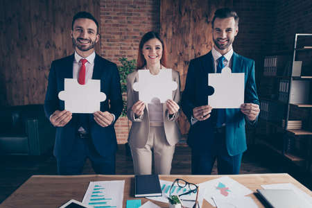 Portrait of three nice chic classy elegant stylish cheerful executive managers holding in hands showing big large puzzle in loft industrial interior workplace workstation Imagens