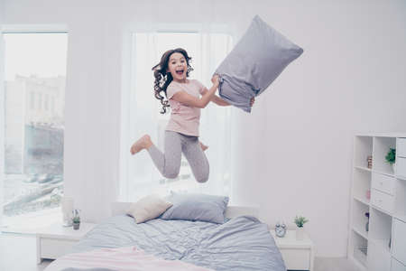 Full length body size view photo funky careless she her little girl jumping high bed  playful curly wavy pillow hands wear home t-shirt pants comfortable apartments flat bright light colored room