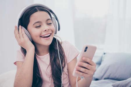 Primo piano foto bella lei la sua bambina smart phone mani paraorecchie occhi chiusi imparare testo nuova canzone popolare riccio ondulato indossare casa t-shirt pantaloni appartamenti confortevoli appartamento luminoso camera dai colori chiari