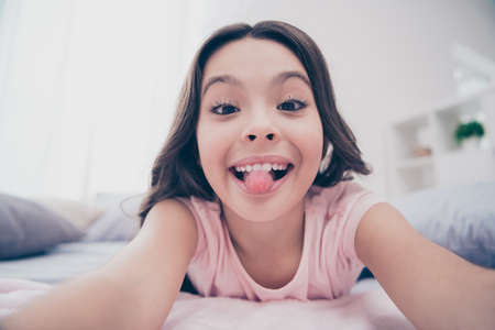 Close up photo cute beautiful she her little girl lying down linen sheets homey sunday make take selfies tongue out mouth wear home t-shirt pants comfortable apartments flat bright light colored room