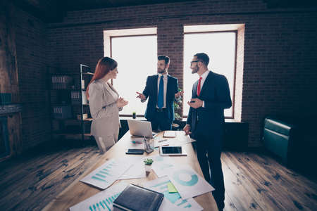 Close up photo three partners she her business lady he him his guys attend course for improving skills listen attentively coacher learn study stand office table wearing formal wear suit. Foto de archivo