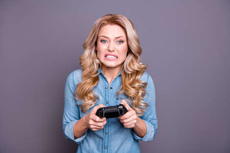 Close-up portrait of her she nice charming attractive worried sad nervous wavy-haired lady wearing blue shirt fan playing game trouble problem loser isolated over gray background