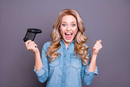 Close-up portrait of her she nice cute charming attractive cheerful wavy-haired lady wearing blue shirt fan playing game great luck opened mouth showing thumbup isolated over gray background Stock Photo
