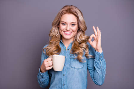 Portrait of nice cute lovely sweet charming attractive cheerful optimistic wavy-haired lady wearing blue shirt holding hot tasty latte cacao cappuccino showing ok-sign isolated over gray  background