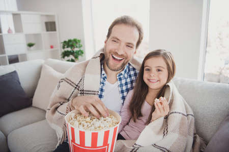 Portrait of his he her she nice cute attractive cheerful cheery positive pre-teen girl handsome bearded dad daddy sitting on divan watching funny cartoon in modern light white interior room indoors Imagens
