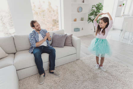 Nice cute sweet lovely attractive cheerful cheery positive stylish elegant pre-teen girl dancing move dad daddy applauding in modern light white interior room indoors