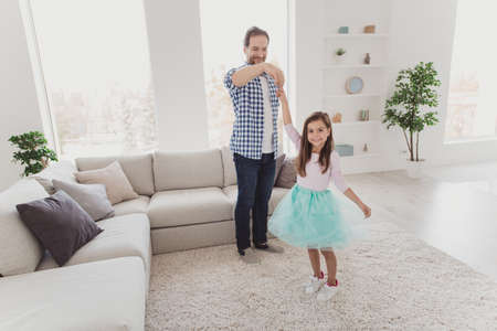 Full length body size view of nice cute lovely adorable attractive cheerful talented stylish elegant pre-teen girl learning practicing moves with dad daddy in modern light white interior room indoors