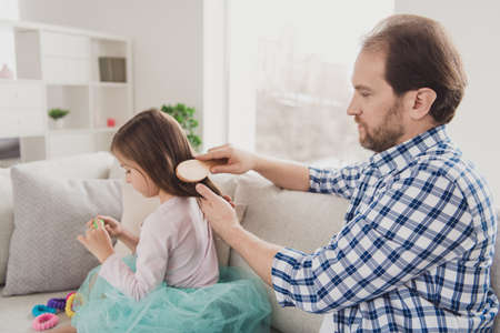 Close up side profile photo little she her girl he him his guy father hair making pigtails ponytails braids morning before kindergarten wear jeans denim checkered plaid shirt house sit cozy divan