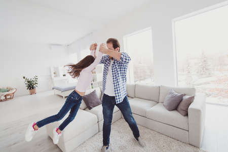 Full length body size view portrait of nice adorable attractive cheerful funny pre-teen girl dad daddy having fun flying daydream dream morning dancing in light white interior room indoors Stock Photo