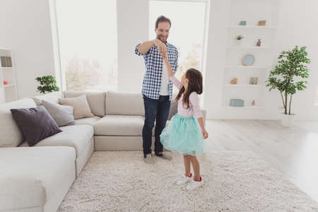 Full length body size view of nice lovely attractive cheerful talented stylish elegant pre-teen girl learning practicing training moves with daddy in modern light white interior room indoors Stock Photo