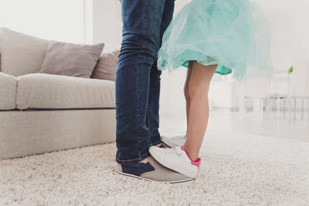 Cropped close-up view of nice two pairs of legs exquisite fashionable trendy stylish elegant pre-teen girl dancing on dads feet trust support in modern light white interior room carpet Stock Photo