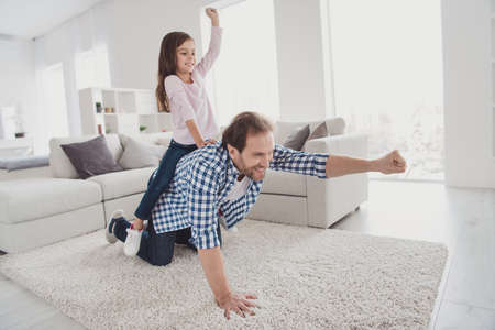 Portrait of his he her she nice lovely attractive pre-teen cheerful cheery positive girl handsome bearded dad daddy having fun on carpet in light white interior room indoors