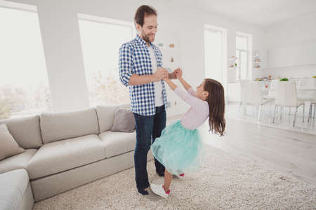 Full length body size view of nice exquisite fashionable attractive cheerful talented elegant pre-teen girl dancing on dads feet trust support in modern light white interior room Stock Photo