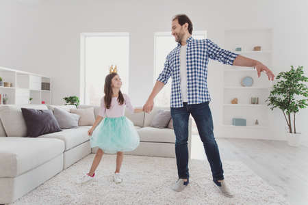 Full length body size portrait of nice lovely attractive cheerful cheery positive pre-teen girl handsome dad daddy holding hands dancing dream holiday in modern light white interior room indoors