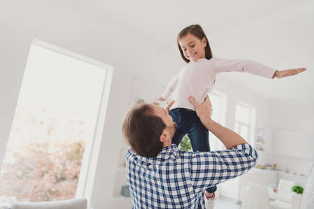 Low below angle view portrait of nice lovely dreamy attractive cheerful cheery positive pre-teen girl handsome bearded dad daddy having fun daydream in light white interior room indoors