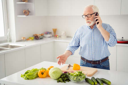 Close up portrait grey haired he his him grandpa concentrated hand arm telephone smart phone tell listen new recipe wear specs casual checkered plaid shirt jeans denim outfit light room kitchen