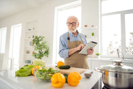Close up photo grey haired he his him grandpa hands arms e-reader noticing changes improving family traditional holiday dish wear specs casual checkered plaid shirt jeans denim outfit kitchen