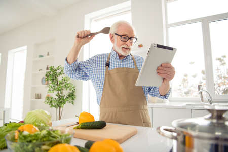 Close up photo grey haired he his him grandpa hands arms e-reader sorry guilty face wrong ingredient afraid scared of consequences wear specs casual checkered plaid shirt jeans denim outfit kitchen