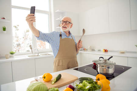 Close up photo grey haired he his him grandpa hands telephone smart phone make take pictures process cooking relatives children wear specs casual checkered plaid shirt jeans denim outfit kitchen 版權商用圖片