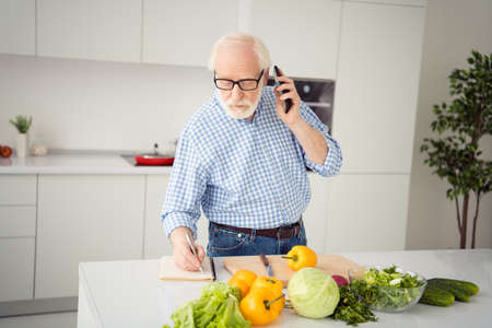 Close up portrait grey haired he his him grandpa hand arm telephone smart phone write down pen family recipe waiting guests wear specs casual checkered plaid shirt jeans denim outfit light kitchen