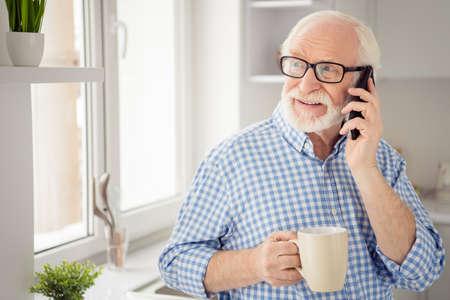 Primer plano retrato de pelo gris él su abuelo bebida caliente mano brazo dígale a los niños estado de salud teléfono teléfono inteligente usuario usa especificaciones casual camisa a cuadros a cuadros jeans mezclilla traje habitación cocina