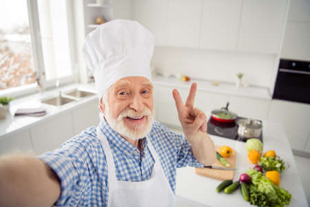 Close up photo cheer grey haired he his him grandpa telephone make take selfies video followers show v-sign say hi wear baker chefs costume casual checkered plaid shirt outfit house kitchen