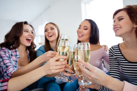 Portrait of nice-looking cute lovely charming attractive cheerful cheery ladies clinking wine wineglass sparkles great event greetings in light white interior room indoors Stock Photo - 119388712