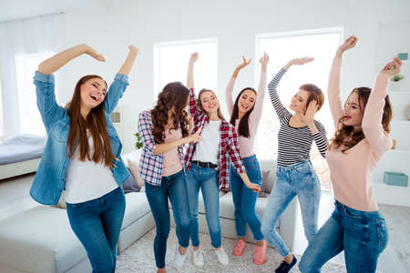 Nice-looking lovely cool charming attractive cheerful glad careless carefree dreamy optimistic girls wearing casual raising hands up rejoicing having fun in light white interior room house indoors