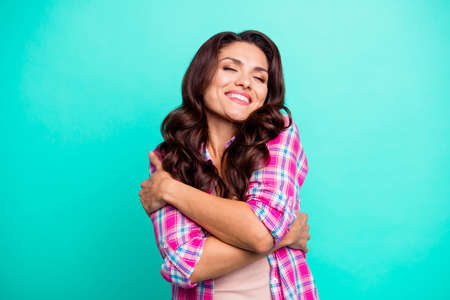 Close up photo attractive amazing she her lady tender hugging herself eyes closed overjoyed wearing casual plaid checkered pink shirt outfit isolated teal green bright vivid background 스톡 콘텐츠