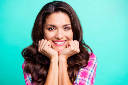 Close up photo amazing she her wavy lady hold cheekbones head on hands arms sweet gentle overjoyed wearing casual plaid checkered pink shirt outfit isolated teal green bright vivid vibrant background