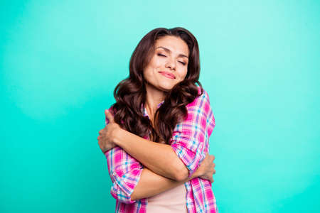 Close-up portrait of her she attractive sweet lovable cheery dreamy fascinating wavy-haired lady wearing checked shirt hugging self isolated on turquoise bright vivid shine background Stock Photo