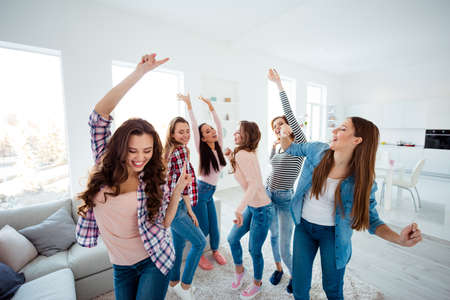 Nice-looking lovely cool charming attractive cheerful glad crazy dreamy optimistic girls wearing casual clothes raising hands up having fun in light white interior room house indoors Foto de archivo