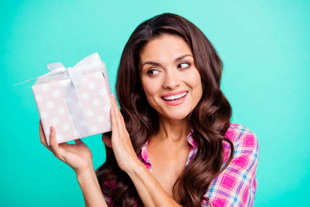 Close up photo beautiful she her lady hold hands arms hold large gift box wonder what inside tricky wish unwrap wearing casual plaid checkered pink shirt outfit isolated teal bright vivid background