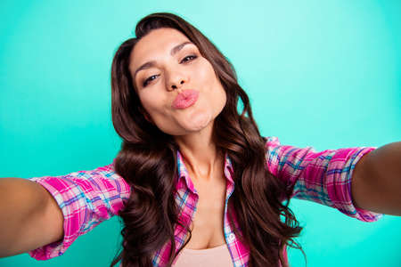 Close up photo amazing beautiful she her lady make take selfies send air kisses pretty boyfriend husband wearing casual plaid checkered pink shirt outfit isolated teal bright vivid background Banque d'images - 119389827