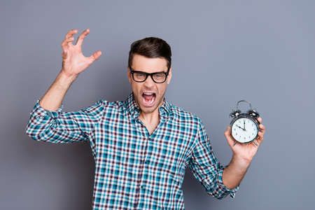 Portrait of his he nice handsome attractive desperate evil guy wearing checked shirt holding in hands ringing clock isolated over gray pastel background Фото со стока