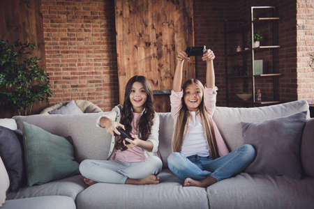 Portrait of two nice pretty lovely sweet adorable attractive charming funny cheerful positive girls sitting on divan playing video game battle crossed legs in house loft industrial interior style