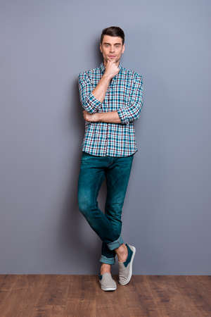 Vertical full length body size photo wondered he him his man arm hand chin perfect hairdo styling easy-going legs crossed wearing casual plaid checkered shirt jeans denim isolated grey background Reklamní fotografie