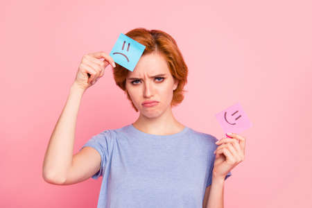 Close-up portrait of her she nice cute charming attractive sad girl wearing casual blue t-shirt holding in hands two draw notes negative bad gloomy choice isolated on pink pastel background