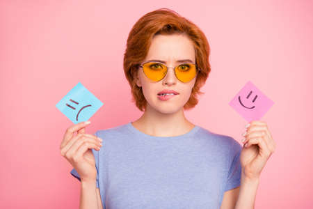 Close-up portrait of her she nice cute charming attractive confused girl wearing casual blue t-shirt yellow glasses holding in hands showing draw note isolated on pink pastel background Reklamní fotografie