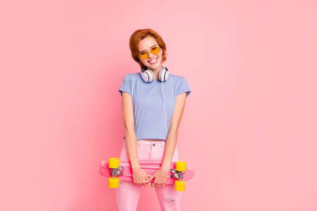 Portrait of her she nice cute charming attractive lovely winsome cheerful cheery girl wearing casual holding carrying skate having fun isolated on pink pastel background