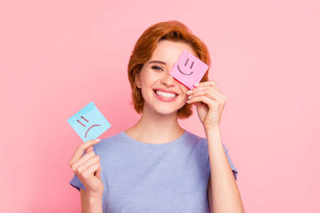 Close-up portrait of her she nice cute charming attractive cheerful girl wearing casual blue t-shirt holding in hands two draw notes positive good choice isolated on pink pastel background