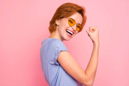 Close-up profile side view portrait of her she nice cute charming attractive lovely cheerful girl wearing casual blue t-shirt yellow glasses showing winning gesture isolated on pink pastel background