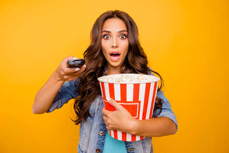 Close up photo beautiful her she lady yell scream shout hold big large popcorn box stupor staring change channel wear blue teal green short dress jeans denim jacket clothes isolated yellow background Stock Photo