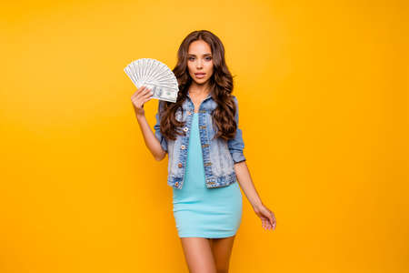 Close up photo beautiful her she lady hold fan money I am wealthy self-confident bossy stunning wear blue teal green short dress jeans denim jacket clothes isolated yellow background