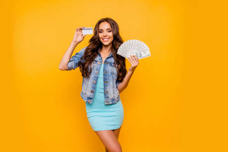 Close up photo beautiful her she lady hold credit card fan money I am wealthy self-confident bossy stunning wear blue teal green short dress jeans denim jacket clothes isolated yellow background