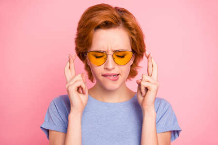 Close-up portrait of her she nice cute charming attractive lovely worried scared girl wearing casual t-shirt yellow glasses biting lip thinking about future isolated over pink background 写真素材