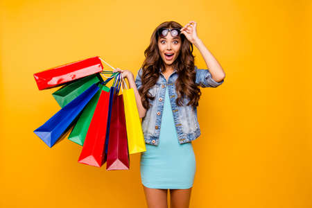 Close up photo beautiful her she lady yell scream shout new staff shopping spree excited big choice choose wear specs blue teal green short dress jeans denim jacket clothes isolated yellow background Archivio Fotografico