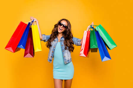 Close up photo beautiful her she lady hands arms enjoy package shopping spree excited amazed low prices wear specs blue teal green short dress jeans denim jacket clothes isolated yellow background Imagens