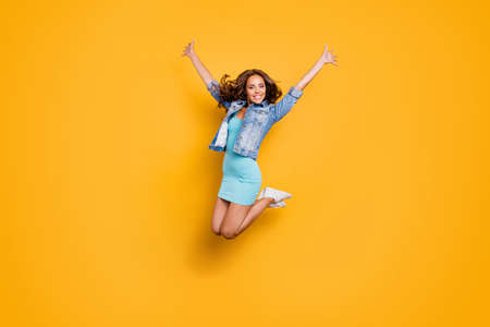 Full length body size photo beautiful her she lady jumping high best cheerleader support ever fan favorite team wear blue teal green short dress jeans denim jacket clothes isolated yellow background
