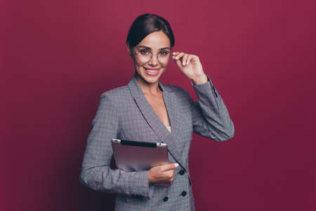 Portrait of her she nice cute attractive lovely sweet cheerful lady ceo boss chief in gray checkered blazer holding in hands ebook touching glasses isolated over maroon burgundy marsala background